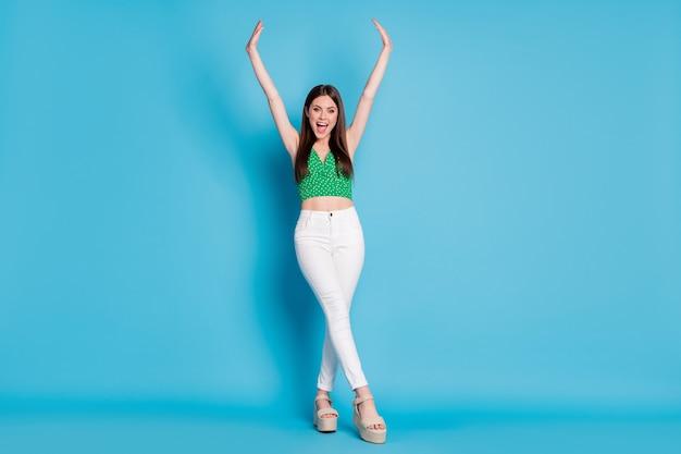 Photo en taille réelle d'une fille folle et candide profitez de votre temps libre pour vous réjouir le week-end crier lever les poings porter de belles chaussures de tenue isolées sur fond de couleur bleu