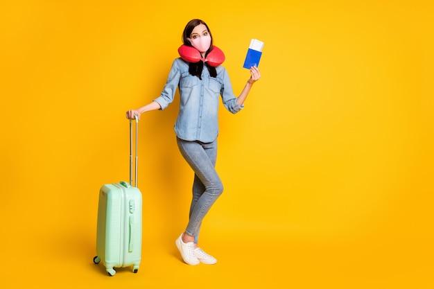 Photo en taille réelle d'une fille tenant un sac de valise billets porter un masque médical coussin de cou
