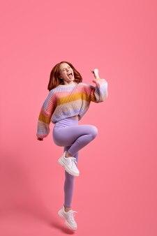 Photo en taille réelle d'une jeune femme aux cheveux roux heureuse crier oui chanceux gagner lever les poings sauter porter des vêtements décontractés...