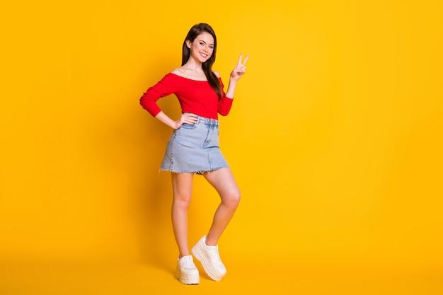 Photo en taille réelle d'une jolie fille séduisante profiter des vacances du week-end faire v-sign porter des débardeurs rouges en denim isolés sur fond de couleur brillante et brillante