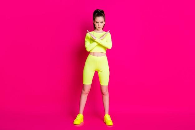 Photo en taille réelle d'une sportive sérieuse, les bras croisés montrent un signal de déclin portant un short jaune isolé sur un fond de couleur rose vif