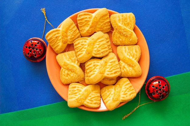 La photo d'un tas de biscuits ou de biscuits sablés sur l'assiette avec des cloches rouges. contexte de la journée nationale des cookies. petit déjeuner de noël pour le père noël.