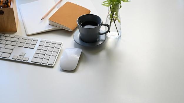 Photo d'une tasse de café, d'un clavier, d'une souris, de notes, d'un crayon et d'une plante en pot réunis sur un tableau blanc moderne. équipement de bureau plat. concept de lieu de travail confortable.