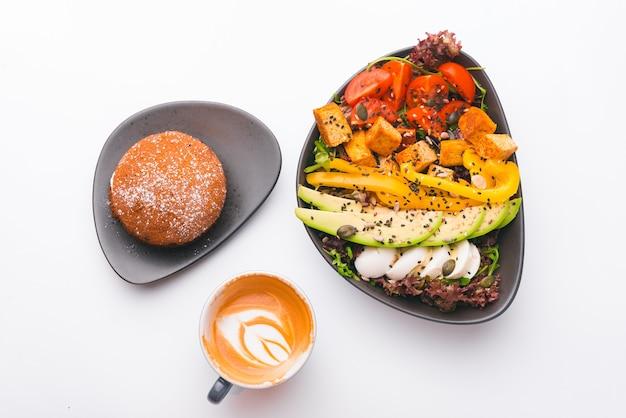 Photo d'une tasse de cappuccino, salade végétarienne fraîche avec tofu avocat et autre et petit gâteau