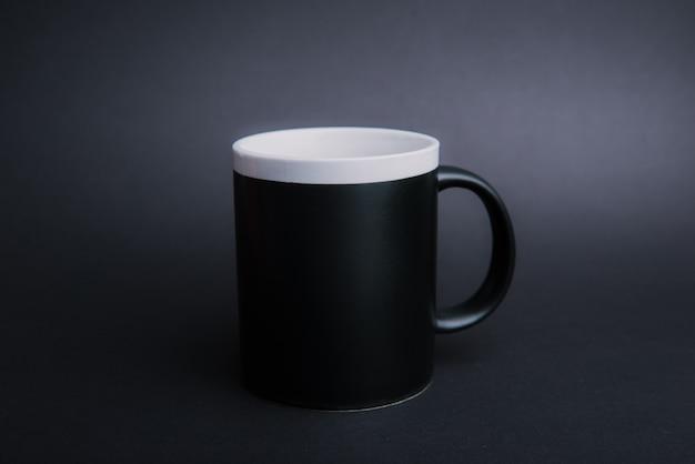 Photo d'une tasse noire sur sombre isolé