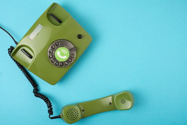 Photo de téléphone vert rétro sur fond bleu