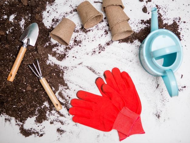 Photo de terre végétale pour la transplantation de plantes, râteau, pelle, arrosoir, gants rouges