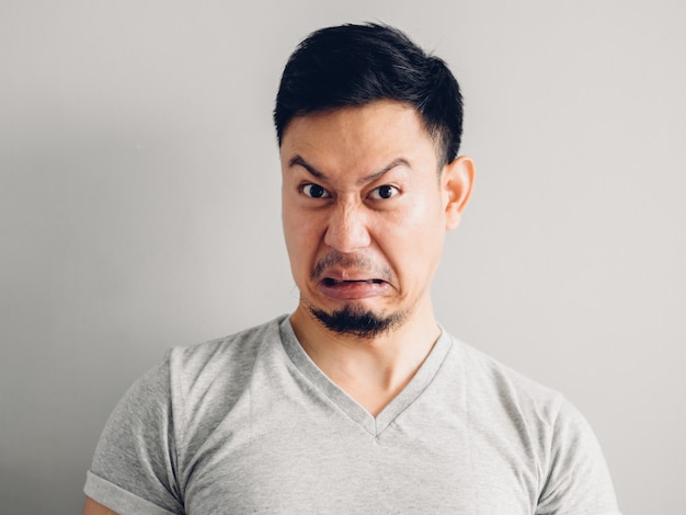 Photo de tête d'homme asiatique avec un visage haineux et dégoûtant. sur fond gris.