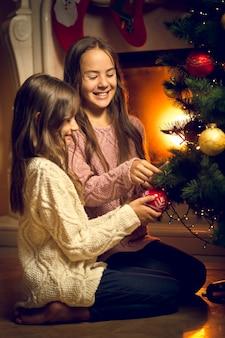 Photo tonique de deux jolies filles assises sur le sol et décorant un sapin de noël