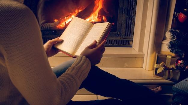 Photo tonique d'une femme lisant un livre à côté d'une cheminée et d'une cheminée en feu