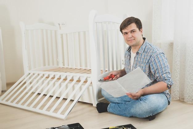 Photo tonique d'un jeune bel homme assemblant lui-même des meubles dans un nouvel appartement