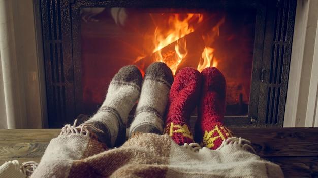 Photo tonique de quelques pieds portant des chaussettes chaudes allongées sous une couverture près de la cheminée en feu