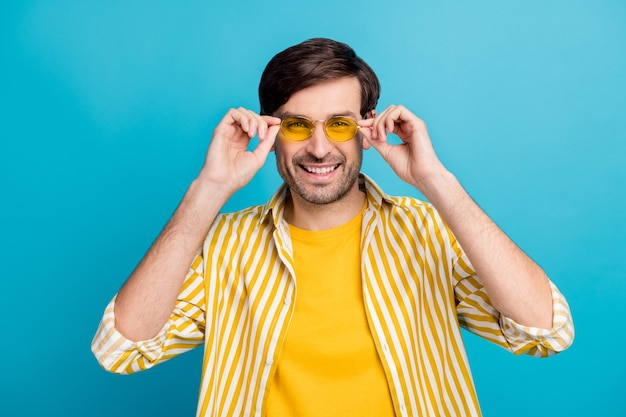 Photo d'un touriste heureux qui touche les spécifications jaunes modernes profiter du repos de voyage se détendre porter une tenue de bonne apparence isolée sur fond de couleur bleu