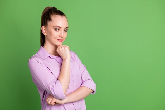 Photo tournée d'une charmante fille de travailleur intelligent toucher le menton de la main prête à penser que les pensées décident de choisir la solution de choix de décision porter des vêtements de bonne apparence isolés sur un fond de couleur verte