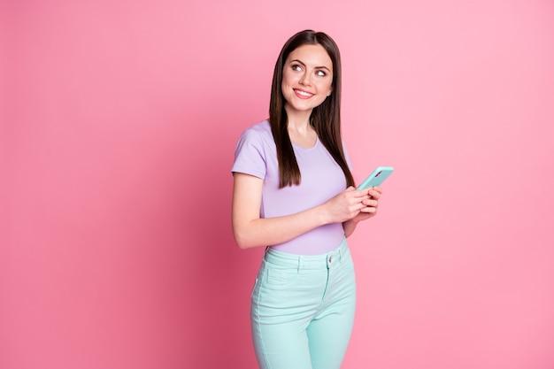 Photo tournée d'une fille joyeuse et positive utiliser un espace de copie de look de téléphone portable imaginer les commentaires sur les médias sociaux porter un pantalon violet sarcelle isolé sur fond de couleur pastel