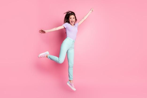 Photo de tout le corps d'une fille énergique et joyeuse qui saute dans la main, essayez d'attraper un parapluie de coup de vent à la mouche de l'air, portez des vêtements violets, des baskets isolées sur un fond de couleur pastel