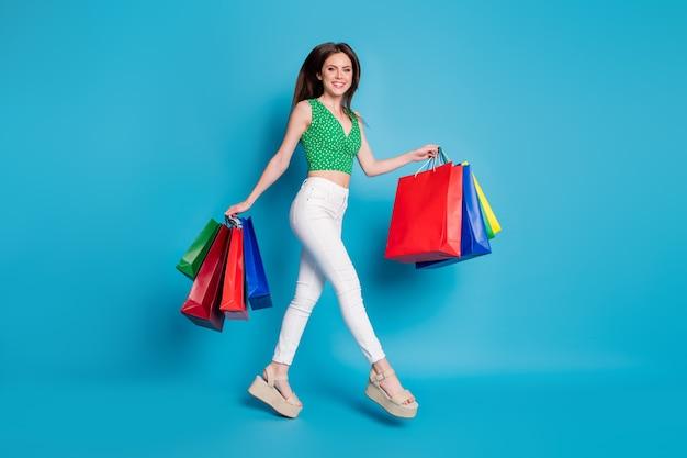 Photo de tout le corps d'une fille joyeuse qui saute dans un centre commercial tenir de nombreux sacs porter un débardeur en pointillé vert singulet pantalon blanc pantalon sandales isolées sur fond de couleur bleu
