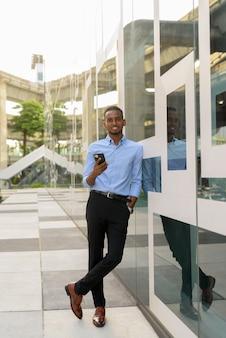 Photo de toute la longueur d'un bel homme d'affaires africain noir à l'extérieur dans la ville pendant l'été souriant et tenant une photo verticale de téléphone portable