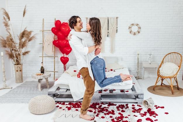 Photo de toute la longueur d'un jeune homme tenant sa petite amie sur les mains dans la chambre décorée de pétales de rose pour la saint-valentin