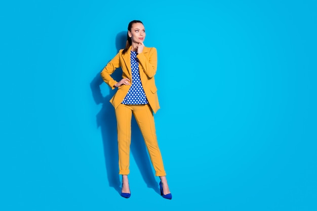 Photo de toute la longueur d'une jolie travailleuse sympathique regarder côté bras de l'espace vide sur le menton porter un blazer jaune pantalon de costume chemisier pointillé chaussures talons hauts isolé fond de couleur bleu vif