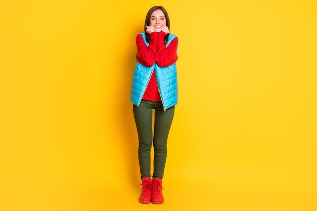 Photo de toute la taille du corps d'une charmante charmante jeune femme regard relaxant mains pommettes visage rayonnant souriant porter un pantalon vert gilet bleu pull rouge bottes isolées fond de couleur jaune vif
