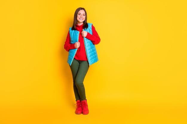 Photo de toute la taille du corps d'une charmante charmante jeune femme souriante enveloppant des vêtements chauds par temps froid porter un pantalon vert gilet bleu pull rouge bottes isolées fond de couleur jaune vif