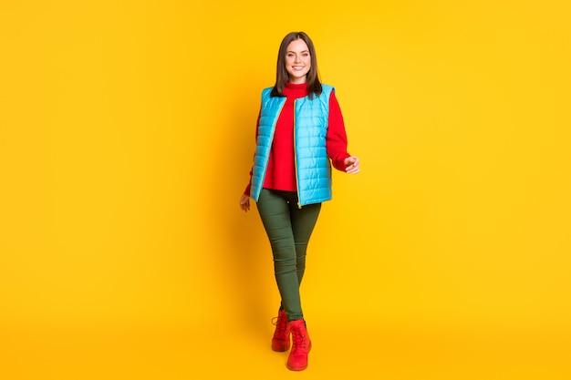 Photo de toute la taille du corps d'une jolie jeune femme souriante souriante marchant élégamment sur la pointe des pieds vers vous portez un pantalon vert gilet bleu pull rouge bottes isolées fond de couleur jaune vif