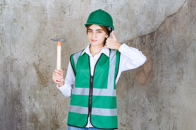 Photo d'un travailleur de la construction en casque vert tenant un marteau