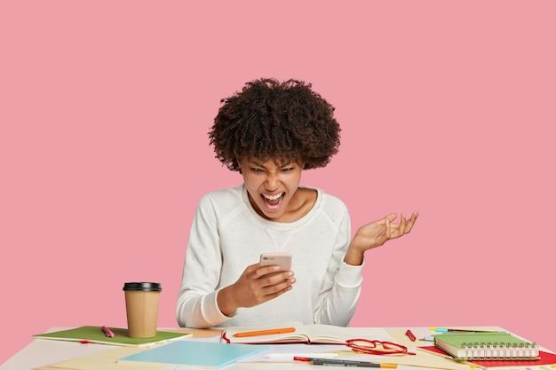 Photo de travailleur féminin noir stressant ou secrétaire regarde l'écran du téléphone intelligent avec irritation