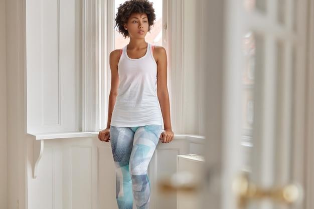 Photo d'un trianer de fitness assez détendu se repose à la maison après l'entraînement, porte un gilet blanc décontracté et des leggings colorés