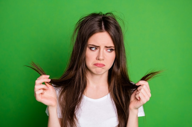 Photo de triste femme irritée habillée tenue décontractée à la tenue de cheveux endommagés bras isolés sur fond de couleur verte
