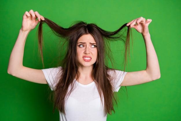 Photo de triste fille irritée vêtue d'un t-shirt blanc à la tenue de cheveux bras secs extrémités isolées fond de couleur verte