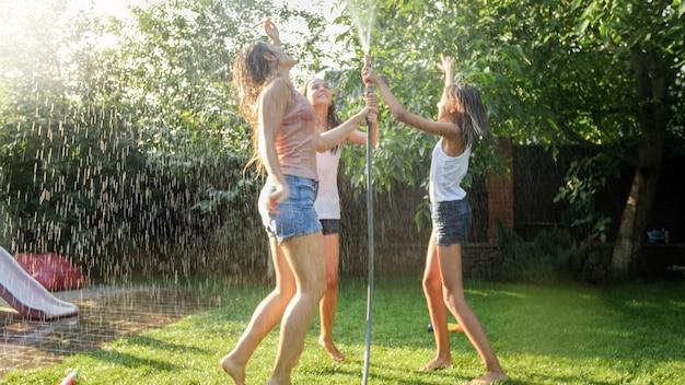 Photo de trois adolescentes gaies dansant dans le jardin d'arrière-cour tuyau d'eau de jardin udner