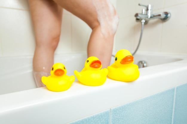 Photo de trois canards en caoutchouc dans la salle de bain avec une femme ayant une douche