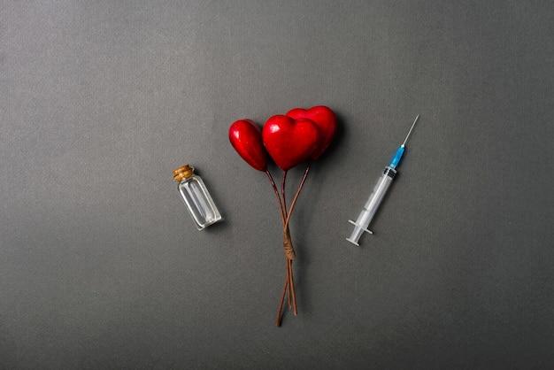 Photo de trois coeurs rouges et vaccin