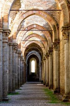 Photo verticale de l'abbaye de san galgano sous la lumière du soleil pendant la journée en italie