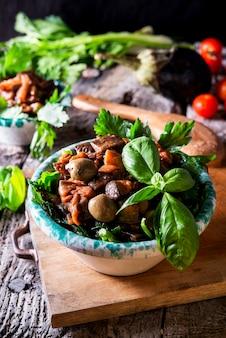 Photo verticale d'une caponata d'aubergine, ypical salade sicilienne image alimentaire sombre rustique