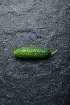 Photo verticale de concombre bio frais sur fond noir.