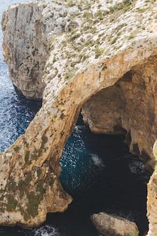 Photo verticale du célèbre mur bleu et point de vue de la grotte à malte
