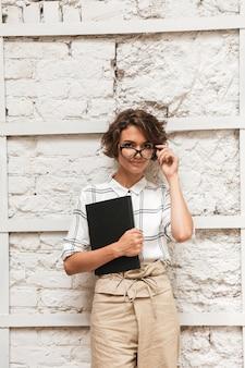 Photo verticale du gestionnaire féminin bouclé songeur