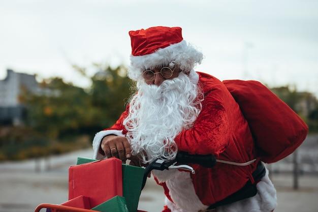 Photo verticale du père noël soutenu dans un vélo plein de cadeaux avec une expression épuisée.