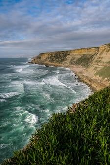 Photo verticale d'une falaise couverte de verdure entourée par la mer sous un ciel nuageux pendant la journée