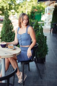 Photo verticale d'une fille. jolie fille dans un haut bleu se trouve dans un café européen. thuyas verts dans un café.