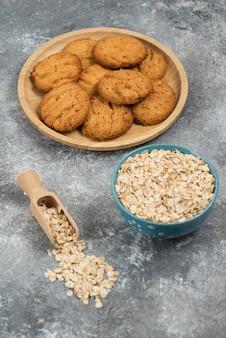 Photo verticale de flocons d'avoine dans un bol devant des biscuits faits maison.