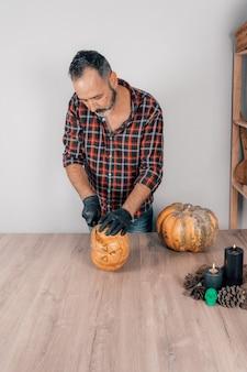Une photo verticale d'un homme adulte avec des gants coupant une citrouille pour halloween