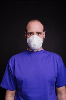 Photo verticale d'un homme avec un masque facial sur un fond sombre - covid-19