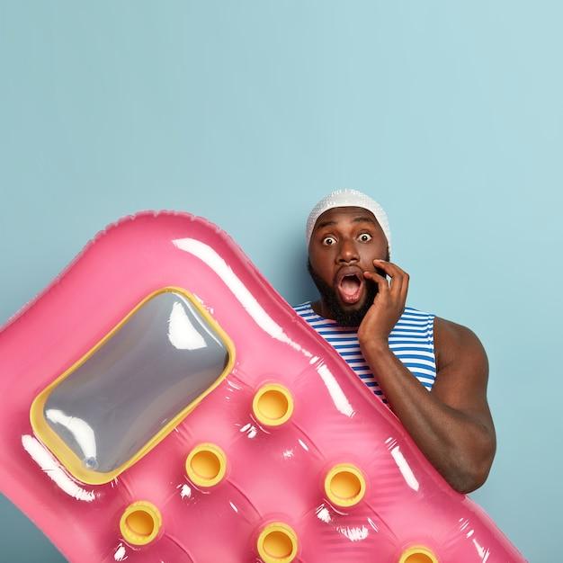Une photo verticale d'un homme noir horrifié perplexe a largement ouvert la bouche