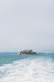 Une photo verticale d'une île au milieu de la mer