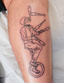 Une photo verticale de la jambe du mâle avec un tatouage squelette en costume jonglant sur une roue
