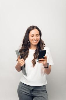 Photo verticale d'une jeune femme naviguant au téléphone tout en tenant son ordinateur portable.